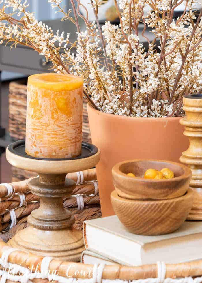 fall vignette with wood candlesticks and bowls and terra cotta planter filled with faux stems